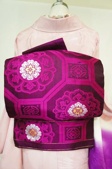 こっくりと深い赤紫色に、光の加減で表情を変え、浮かび上がるように織り出された大胆な唐花蜀江模様が美しい名古屋帯です。