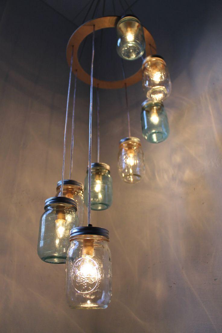 Upcycle de potes de vidro na forma de luminária suspensa em cachoeira espiral. Idealmente seria oportuna a troca das lâmpadas incandescentes por led ou fluorescentes.