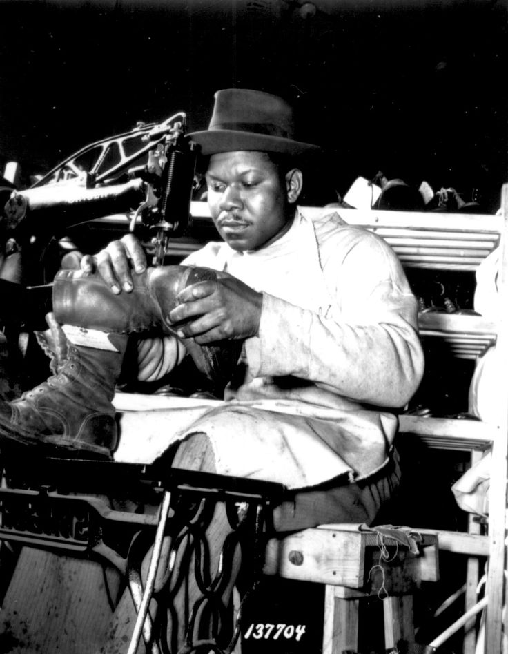 African-American Howard Wilson making a pair of paratrooper boots at a sewing machine in the C & E Shoe Shop at Fort Benning, Georgia, United States, Jul 1942