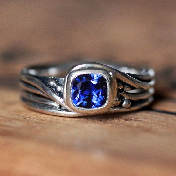 This blue sapphire engagement ring set is made by hand in my NYC studio. An ethical engagement ring from the recycled sterling silver to the lab created Chatham sapphire. The gentle twirling movement of the band coming up to embrace the stone inspired me to call this my Pirouette setting. I created the original using metalsmithing techniques, then had a model made and had it cast into recycled sterling silver. I set a 6mm square cushion Chatham sapphire, oxidized it and gave it a high…