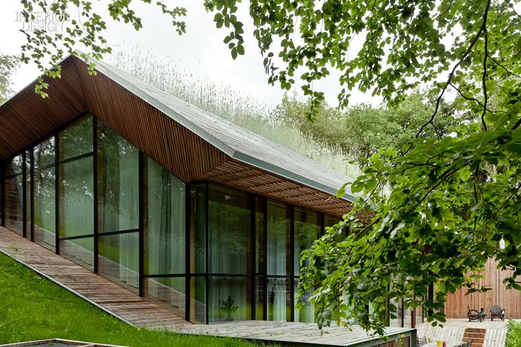 """The exterior of Denieuwegeneratie's """"Dutch Mountain"""" house, which is literally carved out from under a manmade hill, features impressive floor-to-ceiling windows and a welcoming multi-tiered deck."""