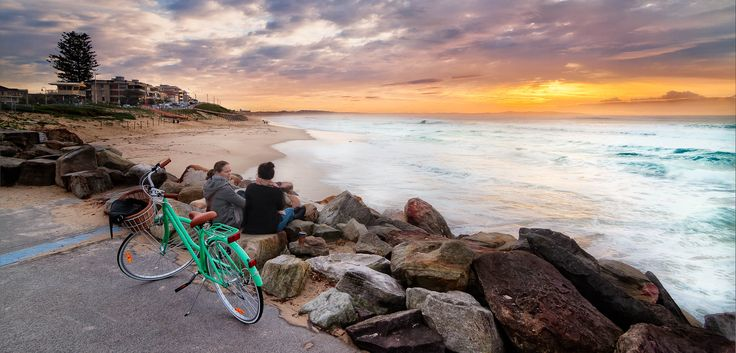 Overlooking the beach in the early morning, and chatting with a friend. This is a wonderful time of day to get out and see a beautiful sunrise. The cruiser bike is a very standard item for beach going individuals. Cronulla NSW Australia