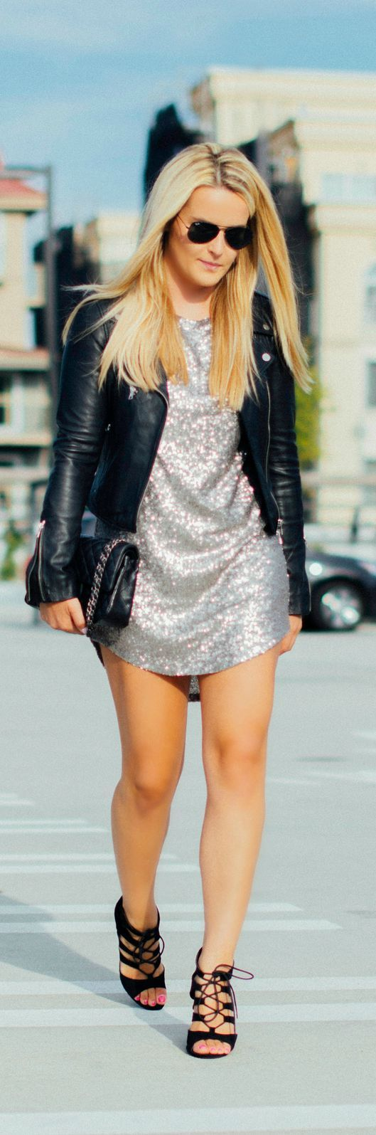 Silver sequins short dress with a black leather jacket. Sandals heels black leather. Fashion Trend.
