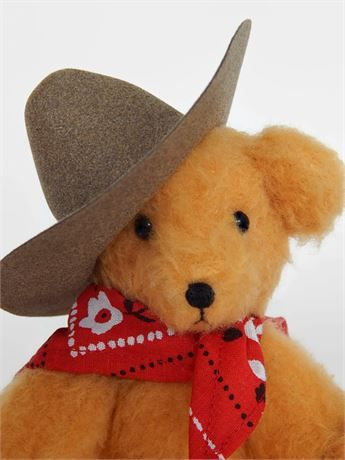 Zane is a miniature string-jointed stuffed plush cowboy bear made from a shaggy gold synthetic plush. This little original handmade artist bear was made as a sitting bear and would look so cute on your desk or anywhere else in your home where you need a friendly face. He is 5 inches in his sitting position not counting his ten gallon hat (7 and 1/4 inches from head to toe). He has black button eyes and a hand-embroidered floss nose. His arms and legs are jointed using upholstery thread. ...
