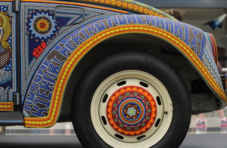 Street and Public Art, Vochol Art Car (detail), Indigenous artisans from the Hichol (Wixaritari) communities of Nayarit and Jalisco, Mexico decorated this car with more than 2 million beads The beads on the outside were applied one at a time on top of resin. The beads on the cars interior were embroidered on fabric. Many of the designs created by the beads are symbolic.