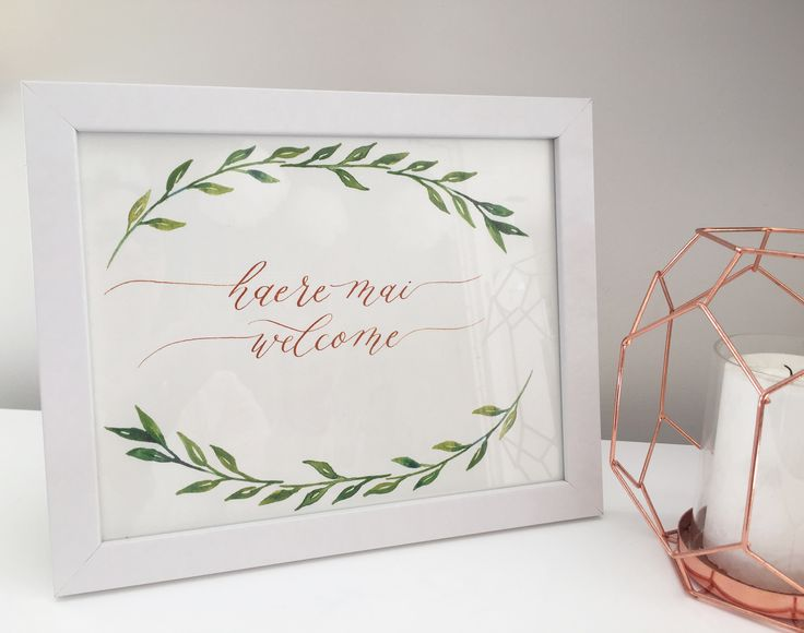 Handwritten calligraphy welcome sign with leaf wreath.