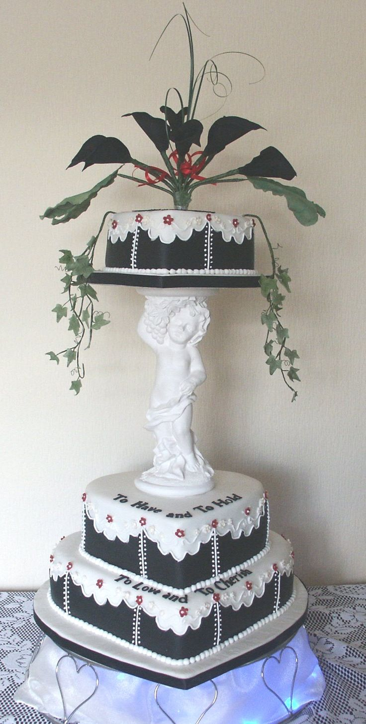 Three tier Heart Shape Wedding Cake with Cherub life to the top tier.  Calla Lilly wire wired sugar flowers to the top tier.  Black and white panel wedding cake
