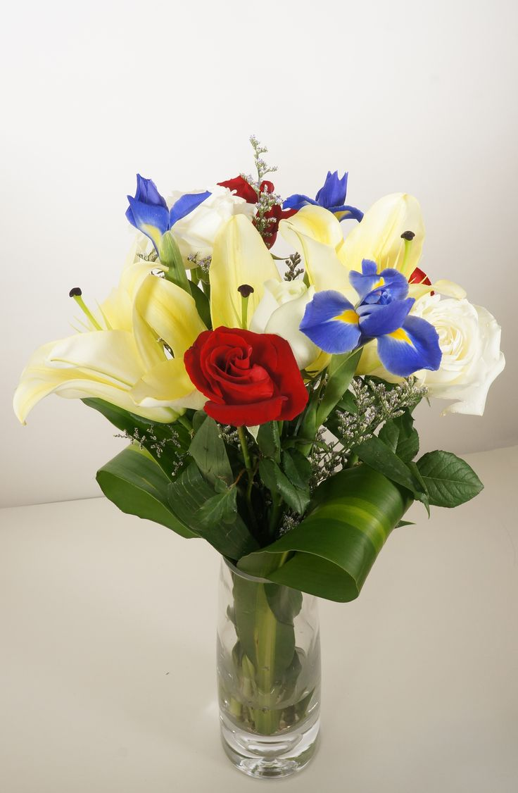 Ariel - Brighten someone's day with this refreshing arrangement of creamy white lilies, violet irises, and assorted color roses. This gift is perfect from new babies to anniversary, and from milestones to marriages. Vase not included.