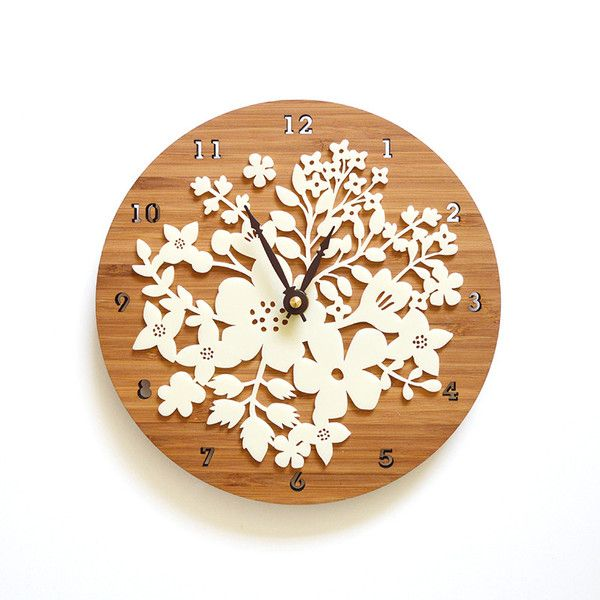 "This beautiful clock features stunning flower motifs. Intricately laser cut while acrylic has a matte finish and it is overlaid on bamboo for a wonderful contrast. FEATURE • Size: 8.5"" wide x 8.5"" tal"