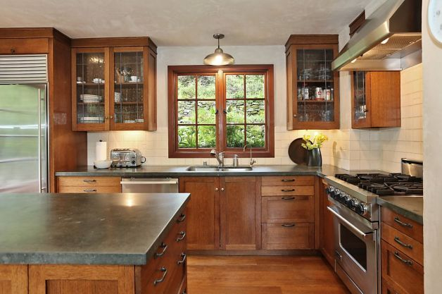 The craftsman renovated kitchen features stainless steel appliances, custom cast concrete counters, warm wood, iron fixtures, wood floor and recessed lighting. Photo: Liz Rusby