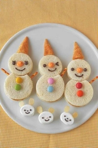 Snowman Sandwiches! Cut-out bread shapes, Bugle snack hats, pretzel arms, Smarties buttons, tiny chocolate chip eyes, large caramel chip nose.