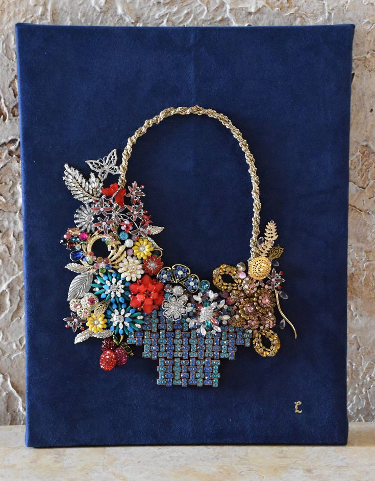 This one-of-a-kind piece from my collection is on a 14 by 18 Artists Loft Canvas. To create this flower basket, I used costume jewelry and vintage costume jewelry (3 pieces). All pieces are glued on to a navy blue suede that is stapled to the canvas. To display this, you can hang on the