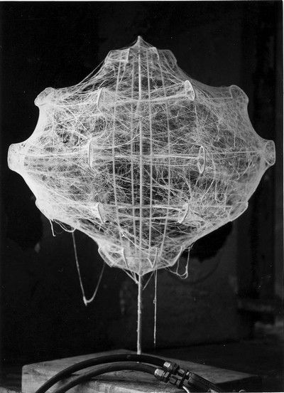 (1960).  The internal structure of the lamps is a slender, white powder-coated steel rod sprayed with the 'cocoon' resin. The result is unusual volumes of shape that were certainly intuited by the designers, but not easily designable without laboratory experiments. In fact, the final shape is the result of a precise intervention: rotating the structure during spraying so that the fibre is thicker in the protruding parts of the structure than in other areas.