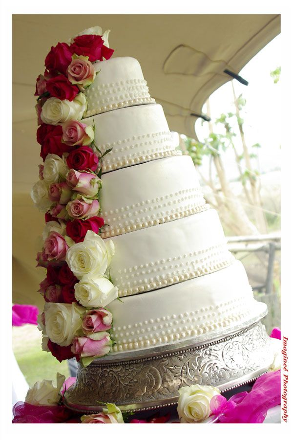 Five tier wedding cake with pink and white roses cascading down the side, placed on a silver round stand  www.iceevents.co.za