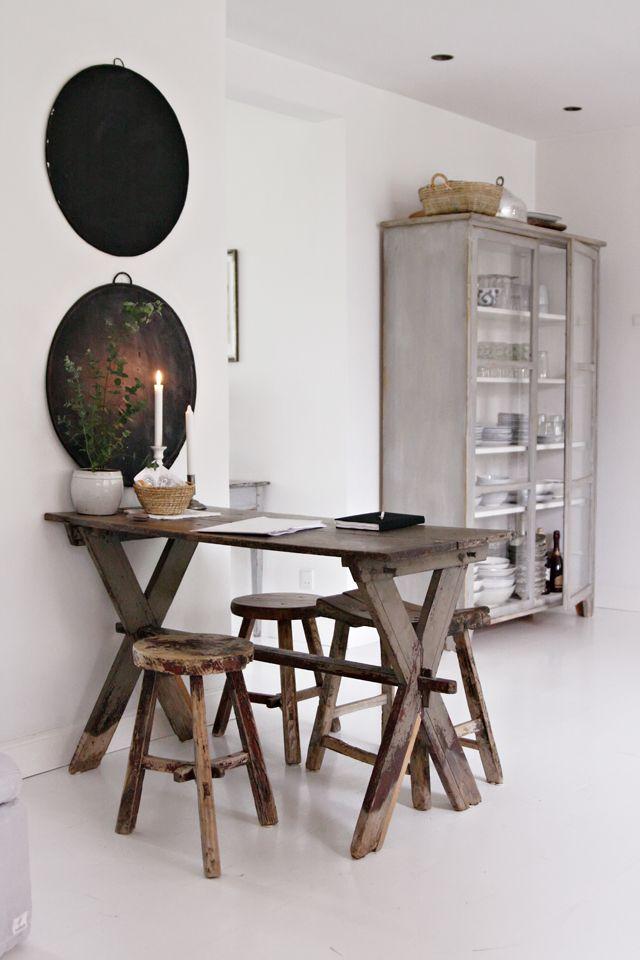 Weiss, Grau und dunkelbraunes Holz. Tisch mit Holzhockern.