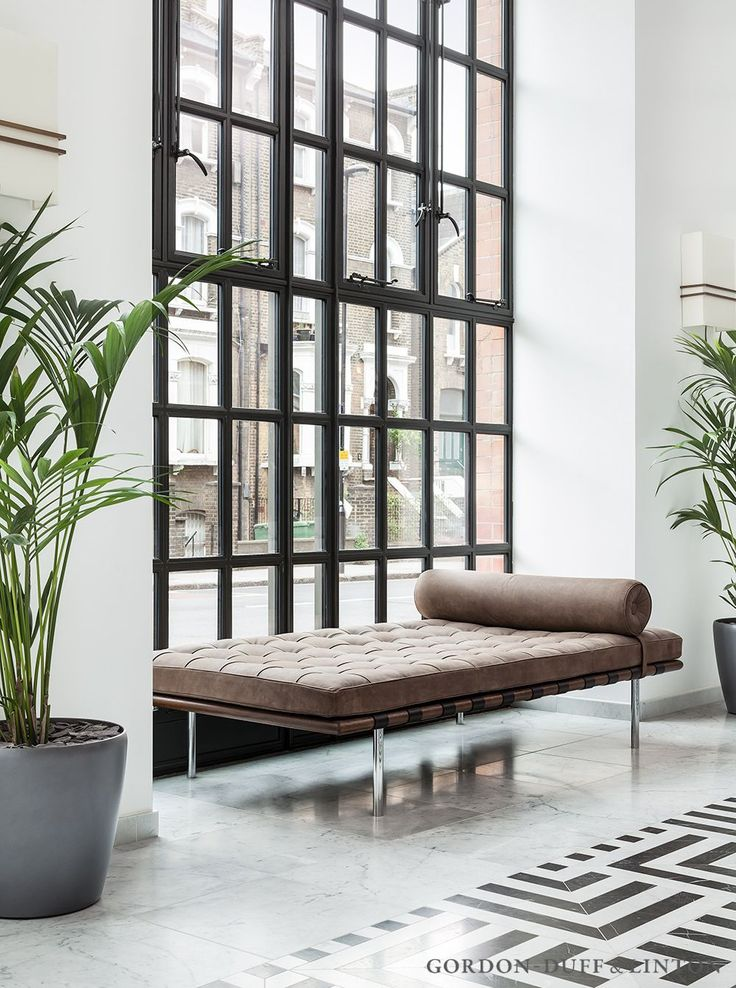 Reception featuring dark grey crittall style windows, grey marquina and carrara marble geometric floor tiles and leather daybeds.