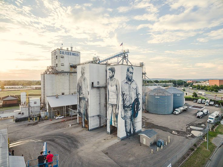 guido van helten paints larger-than-life 'heroes' on feed mill façades in arkansas