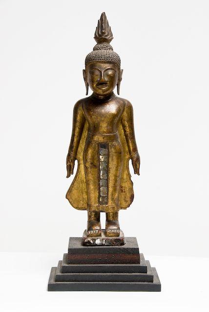 Bouddha en position debout. Style caractéristique de Ban Saï Fong : les deux bras le long du corps, légèrement détaché du corps, paumes vers l'intérieur épousant le mouvement de la toge aux pans évasés vers le bas. Coiffe à petites boucles sphériques, l'unisna est coiffée d'une flamme haute, yeux mi clos aux paupières épaisses, nez camus en bec d'aigle, oreilles ourlées en forme de spirales allongées dont le tragus est le point de départ, les lobes descendants aux épaules. Les phalanges…