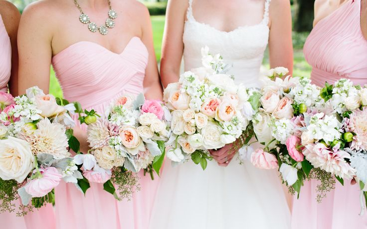 bridesmaids in pink carry bouquets of cafe au  lait dahlia, pink ranunculus, cream spray roses, white stock, white clematis, peach juliette garden rose, dusty miller and seeded eucalyptus.
