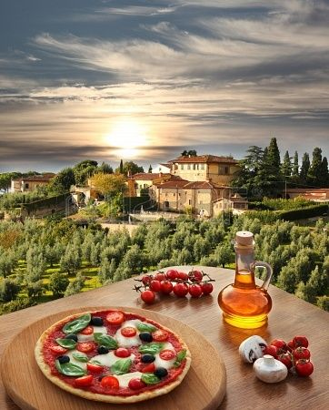 Italian pizza in Chianti against olive trees and villa in Tuscany, Italy.
