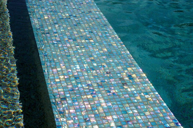 Using iridescent glass tiles on this pool's interior creates a dazzling visual mosaic. Blue Haven Pools & Spas http://www.luxurypools.com/builders-designers/blue-haven-pools-spas.aspx