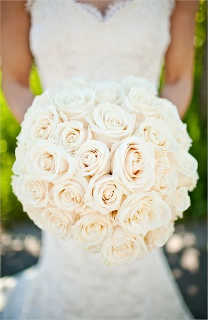 A bride with her stunning wedding bouquet, filled with nothing but romantic white roses  Florist - Dovedale Florist