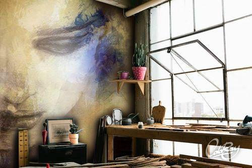 Industrialne wnętrze z pastelową grafiką na ścianie.