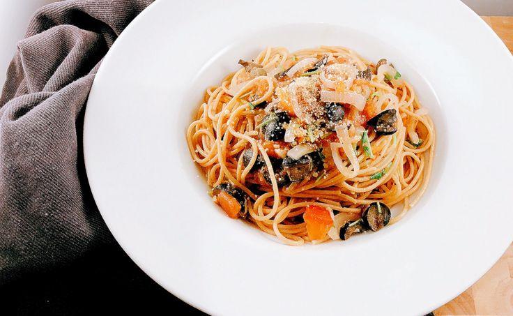 Pasta Puttanesca, een klassiek  Italiaans recept met ansjovis, tomaat, zwarte olijven en parmezaanse kaas.