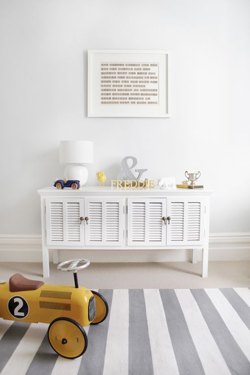 Adorable boy's nursery features art over white toy cabinet accented with louvered doors topped with silver ampersand sign and toys as well as Vilac Retro Ride Car on Crate and Barrel Olin Grey Rug.