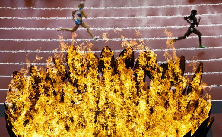 Runners pass by the Olympics flame on the first day of the athletics in the Olympic Stadium at the 2012 Summer Olympics, London, Friday, Aug. 3, 2012. (AP Photo/Daniel Ochoa De Olza)
