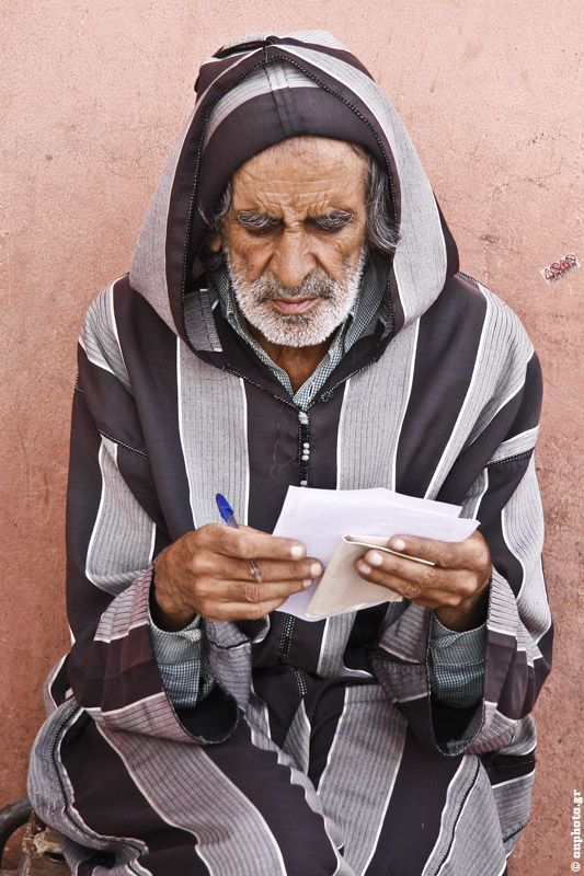 Marrakech; A man is writing/composing a poem for a traditional Moroccan song. He was singing it after he was finishing a sentence.