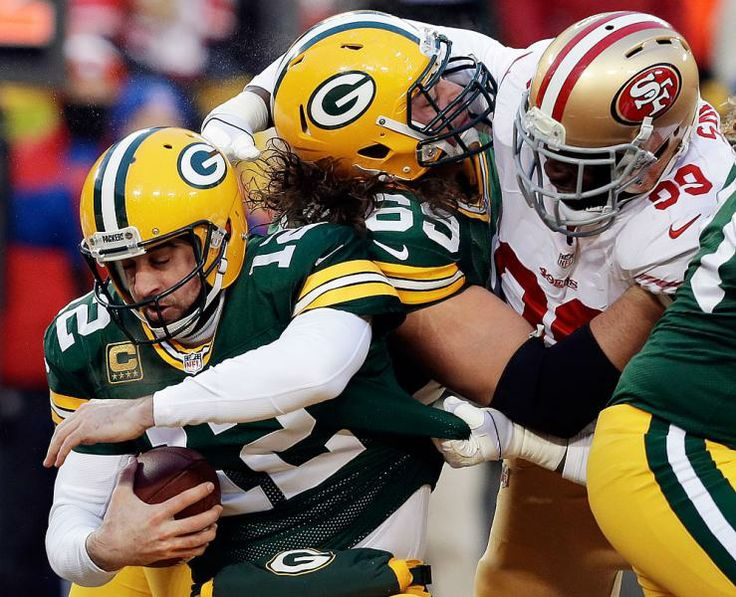 San Francisco 49ers outside linebacker Aldon Smith, right, grabs Green Bay Packers quarterback Aaron Rodgers (12) as Smith fights against the Packers offensive tackle David Bakhtiari