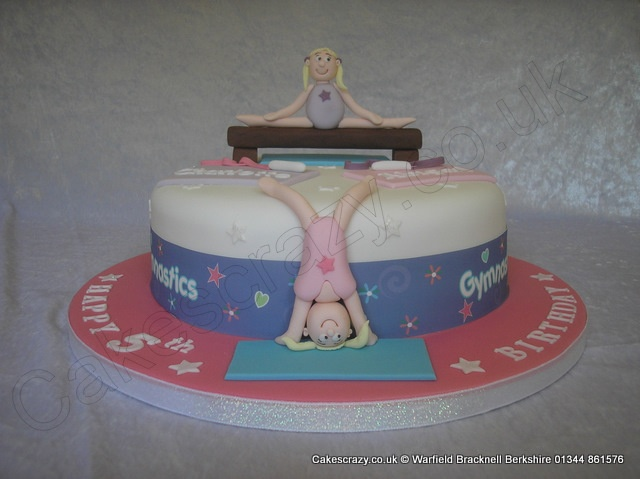 Gymnastics Cake. On the bar... Gymnastics themed character novelty cake on the bar or doing a head stand.  Finished with white glittered stars and gymnastics themed edible sides.