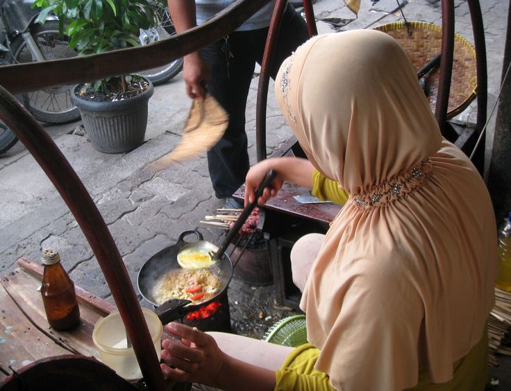 The seller making Tongseng dish (Javanese spicy goat meat soup) in their typical cart in Glodok area, Jakarta. Tongseng is a speciality of Solo (Surakarta) city, Central Java.