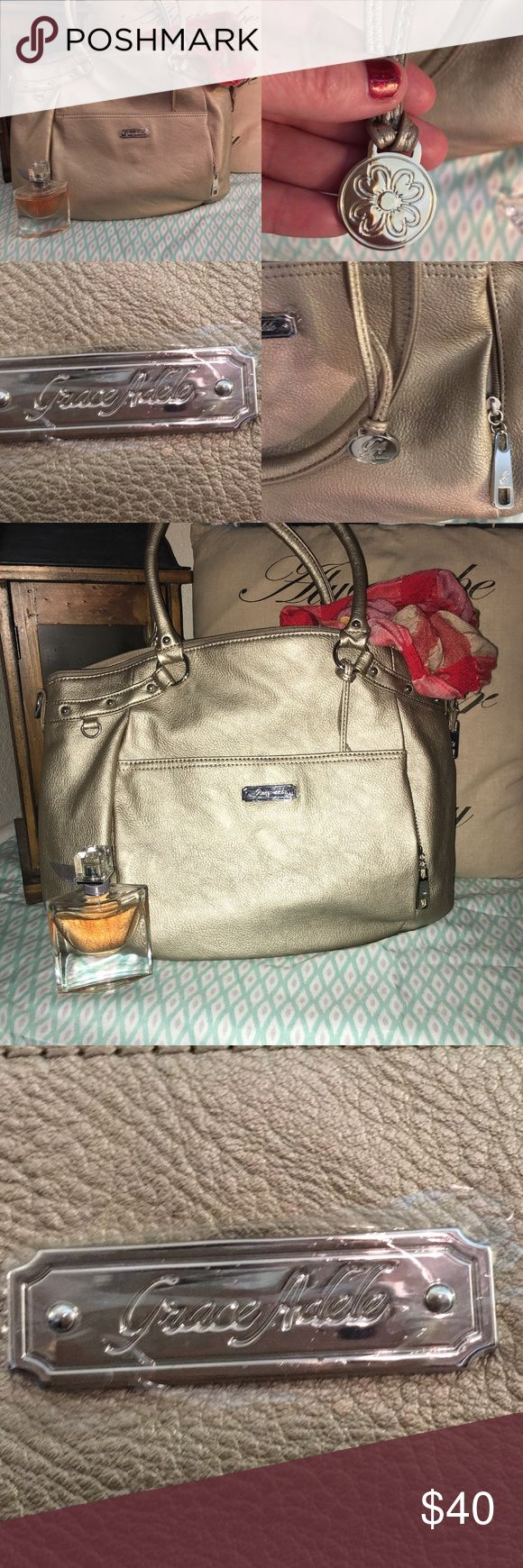 """NWOT/never carried Grace Adele Handbag -make offer NWOT- Never carried, still has plastic on the name plate FLAWLESS inside and out this is LOVELY and  pristine. 17""""L, 12""""H, 5""""W with a 9"""" handle drop.  Vegan Leather. Color is """"metallic"""" includes a bag charm. Tons of storage include a cell phone pocket, and multiple storage pockets.                 ✅Make an offer 🚫Smoke free home! 📦 Same or next Day Shipping from TN 🎸(excludes weekends & Holidays) 🛍- Thank you for shopping my closet Grace…"""