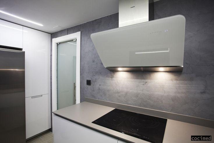En la zona de fuegos combinamos el microcemento de la pared con una encimera de porcelanico de color gris bastante silimar.    La forma de la campana, la iluminación, no poner muebles alto en esa zona, hace que una cocina tan pequeña se vea moderna y lineas muy sencillas. #reformas #cocinas #interiorismo #diseño  #microcemento #ideas #cocimed #alicante