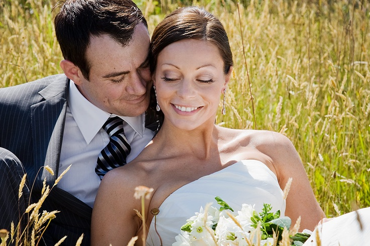 Bride and Groom steal a moment in a grassy field