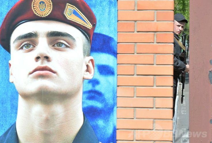 ウクライナ・キエフ(Kiev)近郊で、装飾された射撃練習場の入り口を警備するウクライナの兵士(2014年5月8日撮影、資料写真)。(c)AFP/SERGEI SUPINSKY ▼9May2014AFP ウクライナ親露派、住民投票強行の構え 露の延期要請退ける http://www.afpbb.com/articles/-/3014468