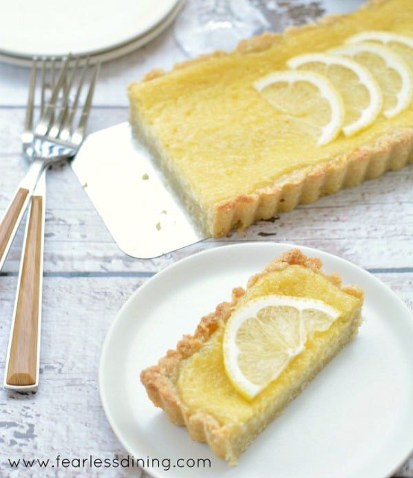 The BEST gluten free lemon tart recipe. You will love how easy this gluten free dessert is to make. Perfect for entertaining. A smooth and creamy, sweet lemon filling on a homemade gluten-free pastry crust.
