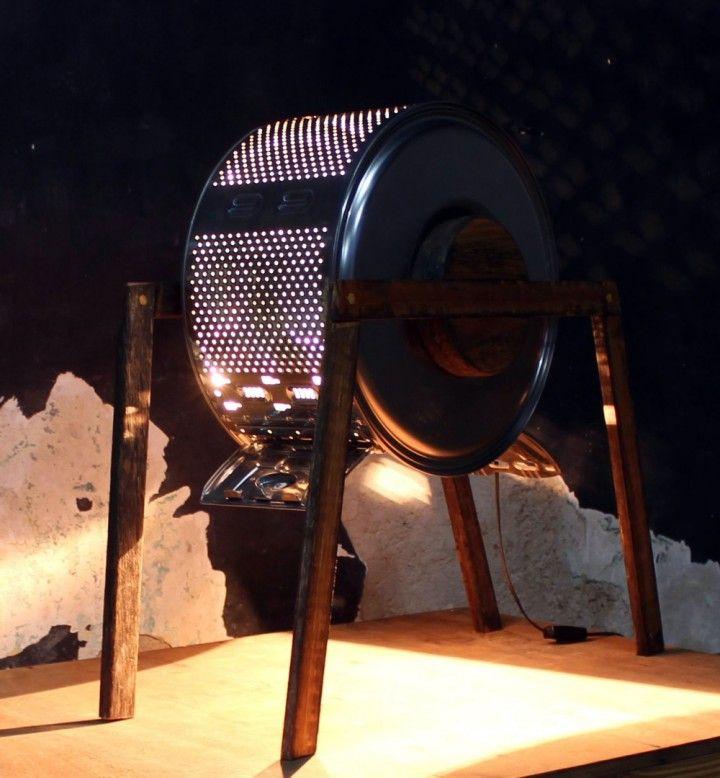 Lámpara de pie.  Hecha con un tambor de lavarropa de carga superior y madera de deck. A diferencia de la mayoría de las lámparas, desde su baja altura esta lámpara dirige su haz de luz principal hacia el piso, acotando muy puntualmente su zona de máxima luminosidad y llenando el resto del espacio con la luz tenue que emiten las aberturas del tambor. Posee un diseño que resalta por lo único y original, demostrando un importante valor artístico agregado.  Altura: 70 cm Base: 60 x 40 cm