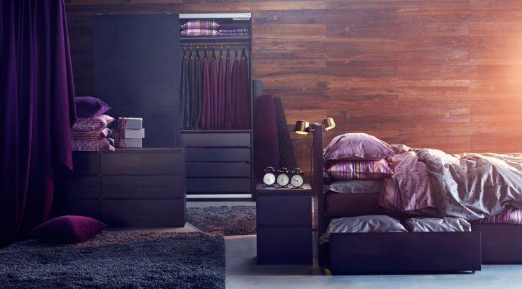 Opstelling met slaapkamermeubilair in paarstinten: houten bed met paars beddengoed, donkergrijze vloerkleden op de grond, garderobekast in donker hout, ladekast en donkerpaarse gordijnen