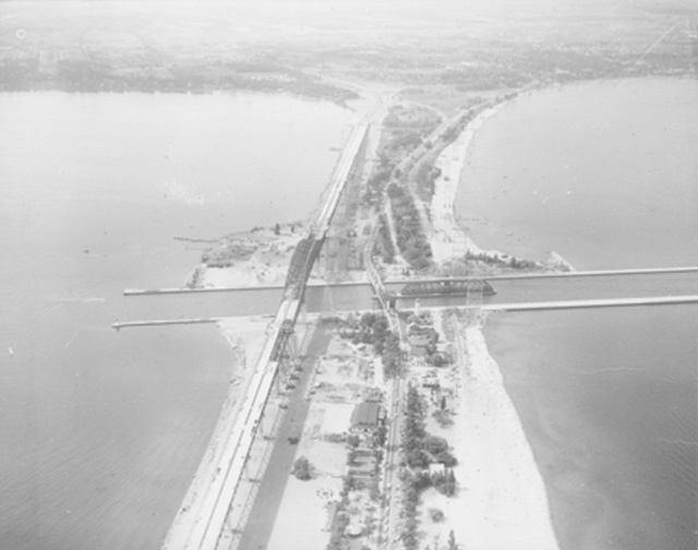 An aerial view of the beach at the canal looking north during the construction of the Burlington Bay Skyway Bridge.