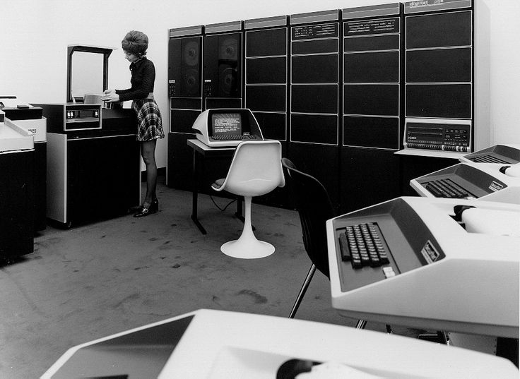Ultra cool 70s computer cafe?  The DEC PDP-11 was beautiful.  Office worker feeding punchcards.  Love the chair, PDP-11 cabinet, and sleek terminals.  This is from the Computer History Museum archive.  The museum is located in Mountain View, CA.  They have some amazing machines - check out coffee table book Core Memory: A Visual Survey of Vintage Computers - photos of the museums collection.