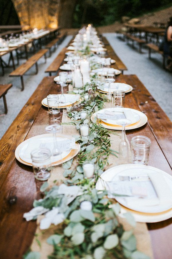 Long bench tables, greenery table garland, candles | Image by Seth & Kaiti Photography