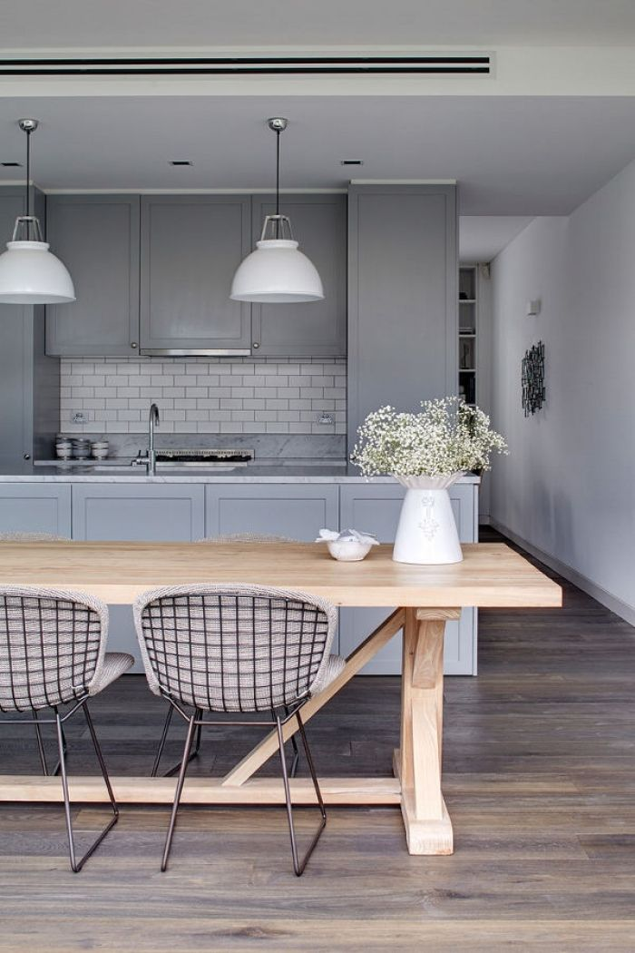 Love the selection of all the items. Gray cabinets with tiles, wood table with textured chairs, vase with flowers and white pendants
