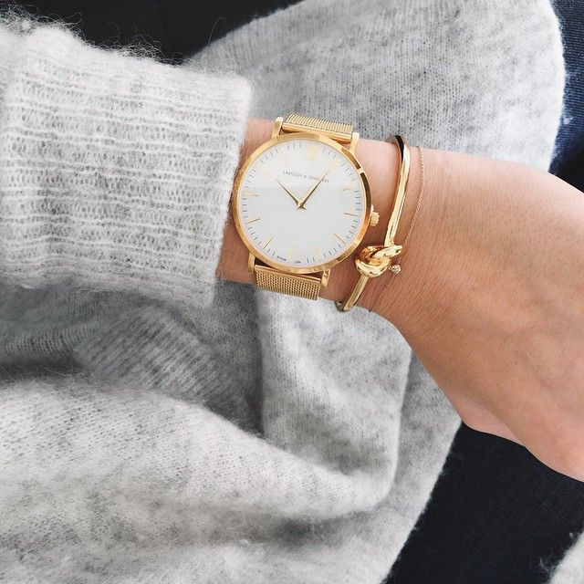 A watch with simple gold bracelets