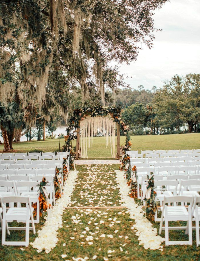 This boho-inspired ceremony features a macrame backdrop + vibrant florals   Image by Shannon Lee Miller