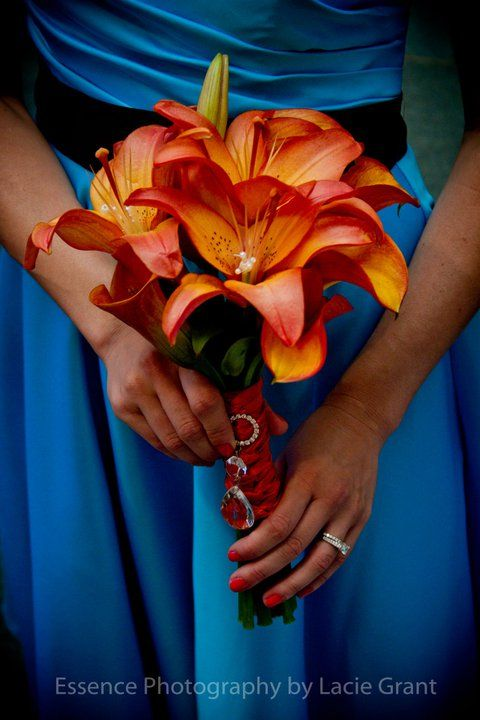 Stunning Sunset lilies and mango calla lilies came together beautifully against this turquoise bridesmaid's dress. The bouquet stems are braided in orange ribbon and accented with rhinestone and crystal prisms. Captured beautifully by Essence Photography by Lacie Grant.