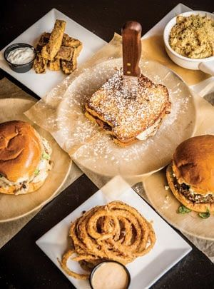 Aaron Quinones offers masterpieces like the #5 burger with bourbon ham, bacon, brie, and egg on French toast (center), as well as killer mac 'n cheese (upper right).