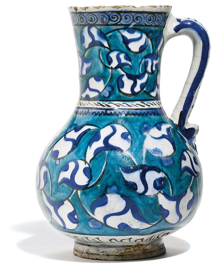 An Iznik polychrome pottery jug with palmettes, Turkey, circa 1580 -    of pear-shaped form with flaring neck and applied serpentine handle on short foot, painted under the glaze in cobalt blue and green with black outlines, featuring entwining palmettes, the neck painted ensuite, the handle with cursory blue dashes, old collection label to underside 19.5cm. height